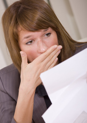 Insurance Policy Review can prevent nasty surprises when making a claim - shocked woman reading a letter